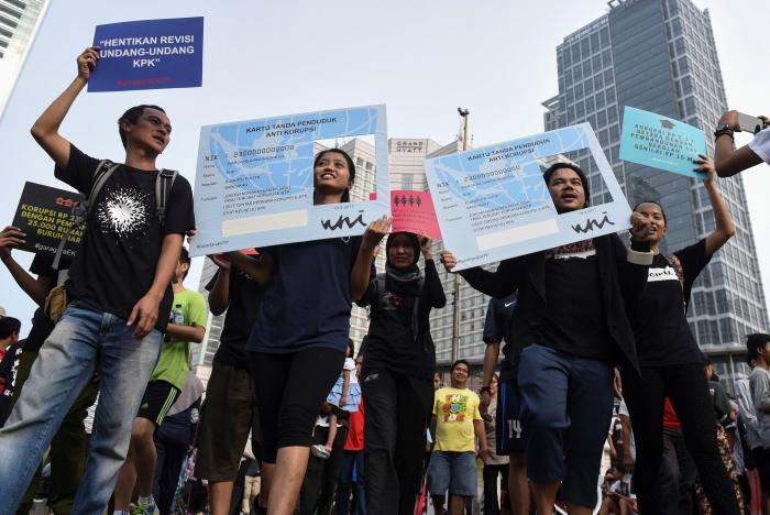 Activists hold placards in the shape of national identity cards (KTP) during a protest calling for the investigation into alleged corruption linked to the procurement of the electronic cards by government officials in Jakarta, Indonesia March 19, 2017 in this photo taken by Antara Foto.   Antara Foto/Hafiz Mubarak/via REUTERS