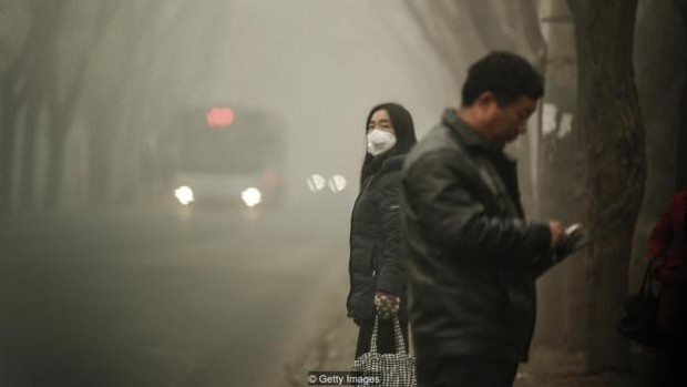 BEIJING, CHINA - DECEMBER 01:  A woman wears a face mask next to traffic shrouded in heavy smog on December 1, 2015 in Beijing, China. China's capital and many cities in the northern part of the country recorded the worst smog of the year with air quality devices in some areas unable to read such high levels of pollutants. Levels of PM 2.5, considered the most hazardous, crossed 600 units in Beijing, nearly 25 times the acceptable standard set by the World Health Organization. The governments of more than 190 countries are meeting in Paris this week to set targets on reducing carbon emissions in an attempt to forge a new global agreement on climate change. (Photo by Lintao Zhang/Getty Images)